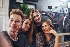 Group of cute teenagers taking selfie with cellphone while sitting in a restaurant with interior in retro style.  Stock Photos