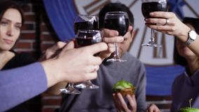 A group of cute young people in a modern restaurant at a table with snacks. Men and girls are baked with glasses of wine. And shouting cheers. Friends celebrate stock video