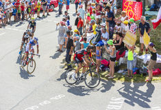 Group of Cyclists on Col du Glandon - Tour de France 2015. Col du Glandon, France - July 23, 2015: Group of cyclists riding on the road to Col du Glandon in Alps Royalty Free Stock Images