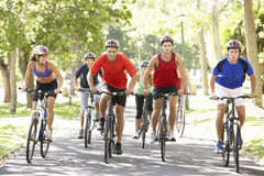 Group Of Cyclists On Cycle Ride Through Park Stock Photo