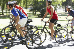 Group Of Cyclists On Cycle Ride Through Park Stock Images