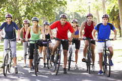 Group Of Cyclists On Cycle Ride Through Park Stock Photography