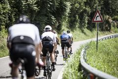 Group of cyclists lined in the italian road. Group of cyclists lined up by a road on a sunny day on his back stock photos