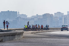 Group of cyclists at Malecon, Havana. A group of cyclists listening to their guide at Malecon in Havana with the buildings of the old town in the background Stock Images