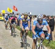 Group of Cyclists- Paris Roubaix 2014. Carrefour de l'Arbre,France-April 13,2014:The Belgian cyclists James Vanlandschoo (Wanty-Groupe Gobert Team) and Jarl Stock Photos
