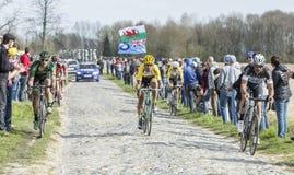 Group of Cyclists- Paris Roubaix 2015. Carrefour de l'Arbre,France - April 12,2015: Group of cyclists riding on the famous cobblestoned road from Carrefour de l' Royalty Free Stock Images