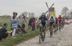 Group of Cyclists - Paris-Roubaix 2018. Templeuve, France - April 08, 2018: Group of cyclists riding in the peloton on the cobblestone road in Templeuve in front Royalty Free Stock Photos