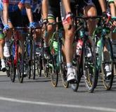 Group of cyclists ride uphill vigorously during the cycling race. The Group of cyclists ride uphill during the international cycling race Royalty Free Stock Image