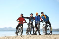 Group of cyclists on shore of a mountain lake. team outdoors. mountain bike stock photos