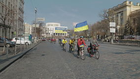Group of cyclists with Ukraine flags. KIEV, UKRAINE - MARCH 22, 2014: Handheld shot of road to The International Convention Center with large revolution banner stock footage