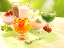 Group of dairy and fruit desserts. With pudding, fruit jelly, shake and joghurt on table with spoon royalty free stock image