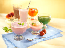 Group of dairy and fruit desserts. With pudding, fruit jelly, shake and joghurt on table with spoon royalty free stock photos