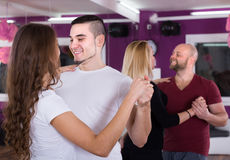 Group dancing in club. Group of smiling positive young adults dancing salsa in club Royalty Free Stock Photography