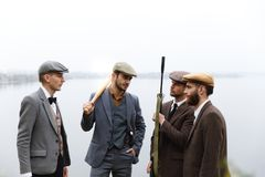 A group of gangsters in suits and with weapons are discussing something. Retro. Outdoors. A group of dangerous gangsters in suits and with weapons are Royalty Free Stock Images