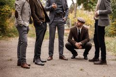 Group of dangerous retro gangsters in the park. All are naught except for one man. Squatting looks at friends Stock Image
