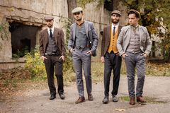 A group of dangerous retro gangsters are walking in the park. A group of dangerous retro gangsters are walking in the park with their hands in the pockets of Royalty Free Stock Image