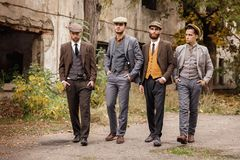 A group of dangerous retro gangsters are walking in the park. A group of dangerous retro gangsters are walking in the park with their hands in the pockets of Royalty Free Stock Photos