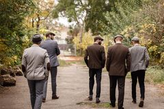 Group of dangerous retro gangsters in the park, view from the back. Stock Photography