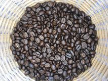Group of dark roasted coffee bean in bamboo woven basket royalty free stock images