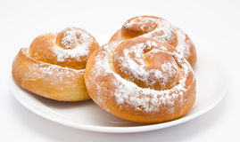 Group of delicious cinnamon rolls icing sugar on plate isolated Stock Image