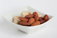 Group of delicious nuts on a white plate. Closeup Royalty Free Stock Photos
