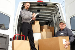 Group of delivery men near shipping truck. Group of delivery men with parcels near shipping truck. Parcel service royalty free stock photos