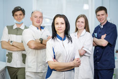 Group of dentists standing in their office and looking at camera. Royalty Free Stock Images