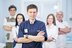Group of dentists standing in their office and looking at camera. A group of dentists in uniform, men and women team, in the office of the dental clinic Royalty Free Stock Images