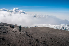 Group descending from summit of Kilimanjaro. Walking back along the rim of the crater above the glaciers to Stella Point and the descent route back to camp at Royalty Free Stock Photography