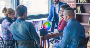 Group of creative designers discuss the color palette in a moder. Group of designers discussing a new color palette in the workplace in a modern office royalty free stock photography