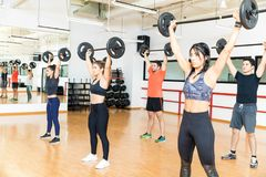 Determined Men And Women Lifting Barbells In Gym. Group of determined men and women lifting barbells together in gym stock images