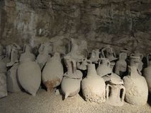 Group of different antique amphoras in the cave. royalty free stock image