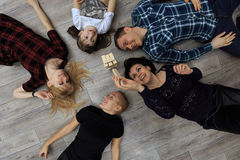 Group of different friends, adults and child, play bricks game on floor. Horizontal top view, concept of friends or family having fun together royalty free stock photos
