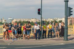 A group of different people is waiting for a pedestrian traffic light. stock images