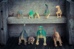 Group of dinosaurs on wooden shelf. In vintage style Stock Photos