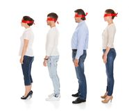 Group Of Disoriented People. Group Of A People With Red Ribbon Tied On Eyes Isolated Over White Background Stock Images