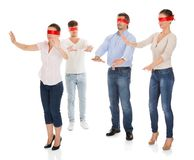 Group Of Disoriented People. Group Of A People With Red Ribbon Tied On Eyes Isolated Over White Background Royalty Free Stock Images