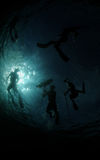 Group of divers underwater spearfishing Stock Photos