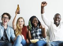 Group of diverse friends drinking and cheering while watching sports together Royalty Free Stock Image