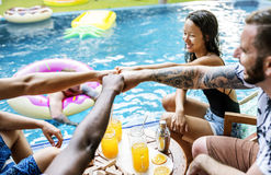 Group of diverse friends enjoying summer time by the pool Stock Photos