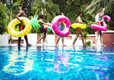 Group of diverse friends enjoying summer time by the pool with i. Nflatable tubes Stock Image
