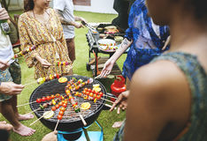 Group of diverse friends grilling barbecue outdoors Stock Images
