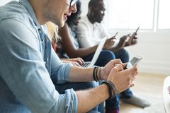 Group of diverse friends hanging out and using digital devices Royalty Free Stock Photography