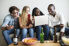 Group of diverse friends hanging out and using digital devices Royalty Free Stock Photo