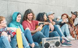Group of diverse friends having fun outdoor - Millennial young people using mobile phones and listening music with vintage boombox