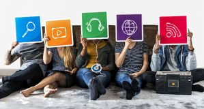 Group of diverse friends holding technology icons