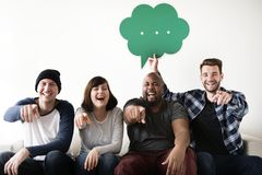 Group of diverse friends laughing pointing finger at the camera holding a speech bubble icon Royalty Free Stock Images