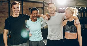 Group of diverse friends laughing while standing in a gym