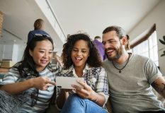 Group of diverse friends playing game on mobile phone Royalty Free Stock Photography