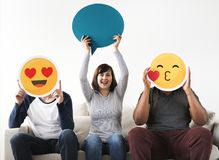 Group of diverse friends sitting on couch with emoticon internet and connection concept Stock Image